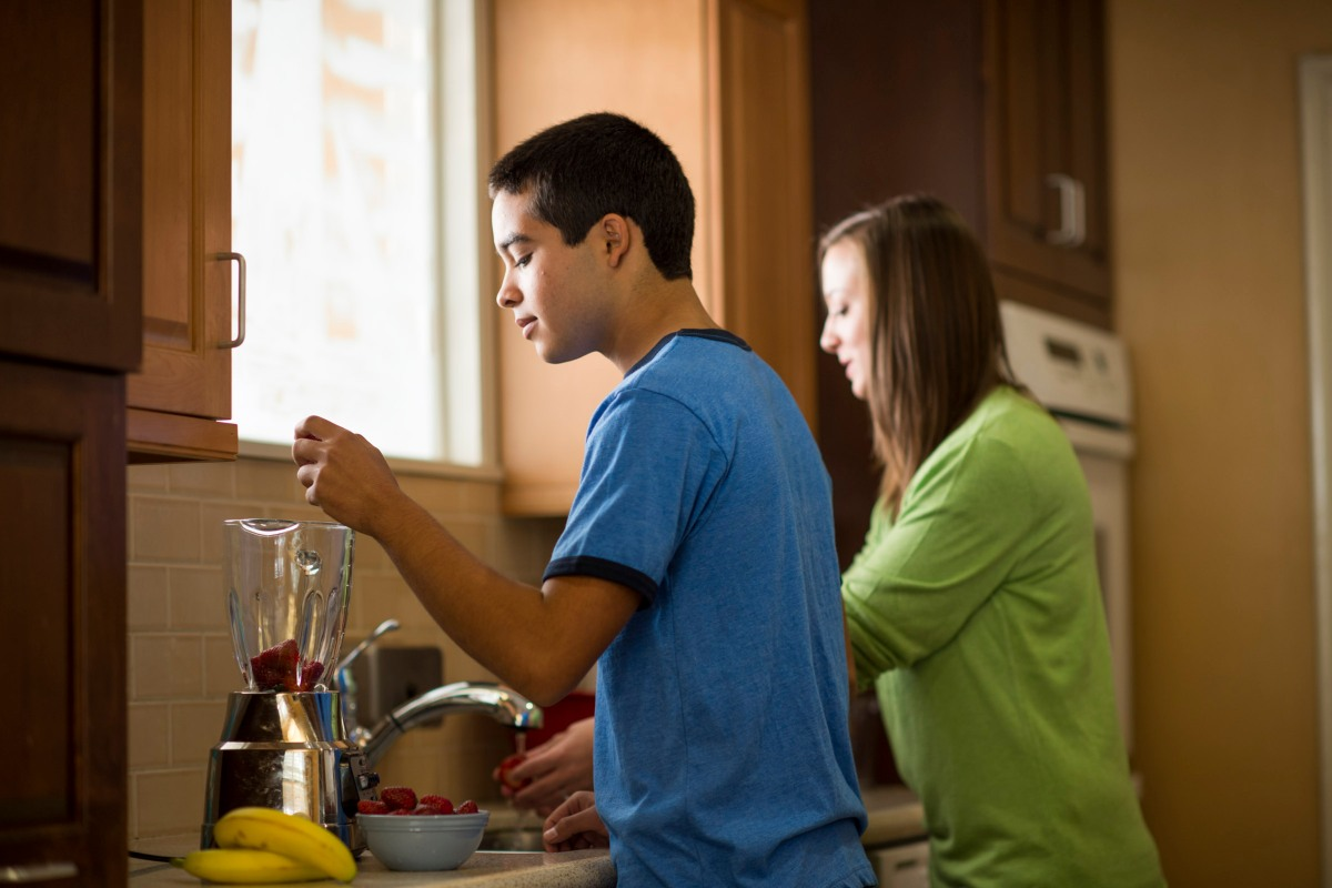 A Hillsides child care worker helps a youth make a healthy snack.