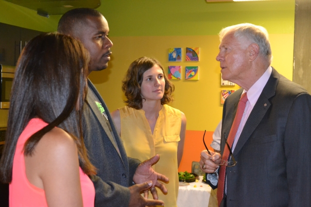 Thomas Lee, division director of transition-aged youth services (second to left), shares information on Youth Moving On's Peer Resource Center to Los Angeles Board of Supervisor Michael Antonovich (right). Looking on are Monigue Holguin (left) and Jessica Petrass from Youth Moving On.